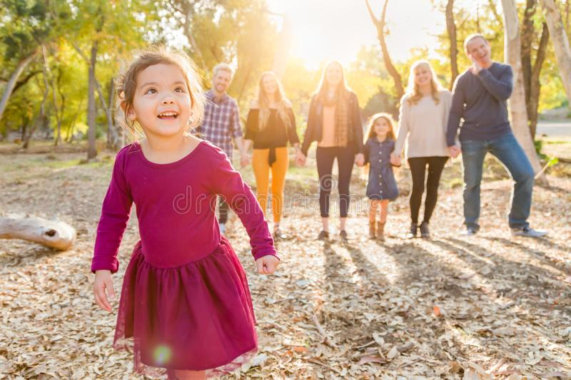 Mixed Race Baby Girl Outdoors with Family Behind stock images