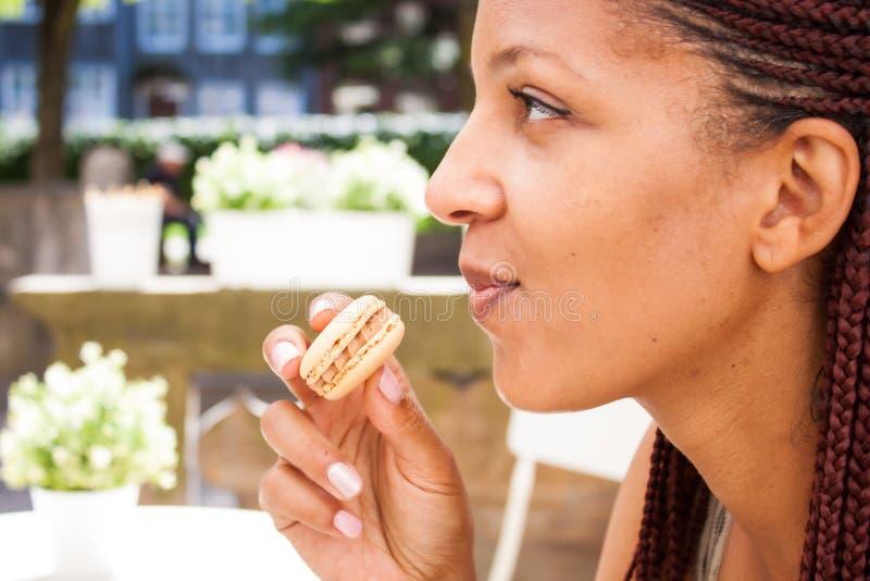 Girl eating macaron. Mixed race beautiful girl eating chocolate macaron in summer outdoor cafe royalty free stock image