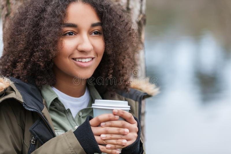 Mixed Race Biracial African American Teenager Drinking Coffee Outside. Beautiful happy mixed race biracial African American girl teenager female young woman stock photography