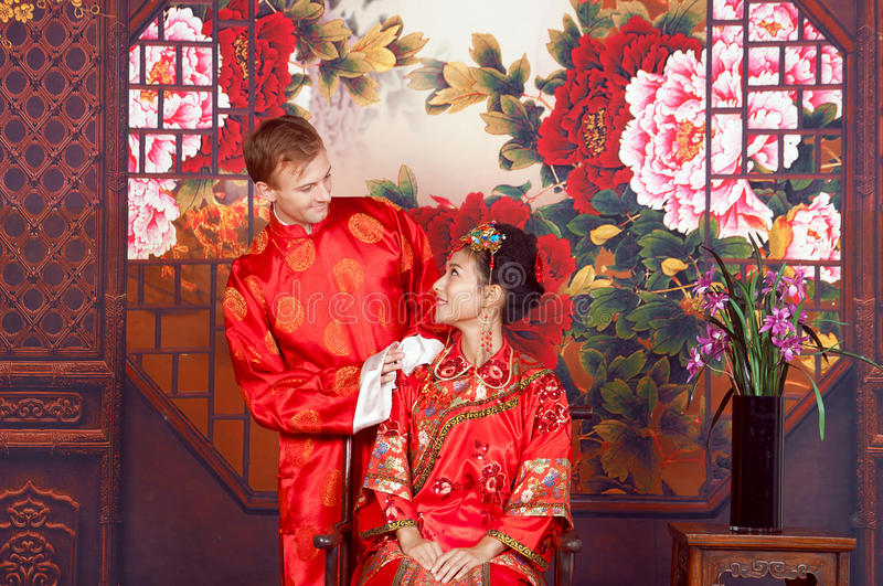 Mixed Race Bride and Groom in Studio wearing traditional Chinese wedding outfits.  royalty free stock photography