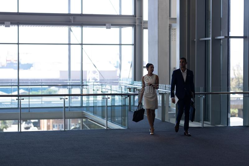 Mixed-race business people walking together in modern office stock photos
