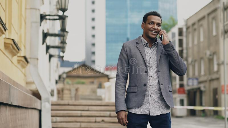 Mixed race businessman talking at smartphone and feels happy about making deal outdoors royalty free stock photography