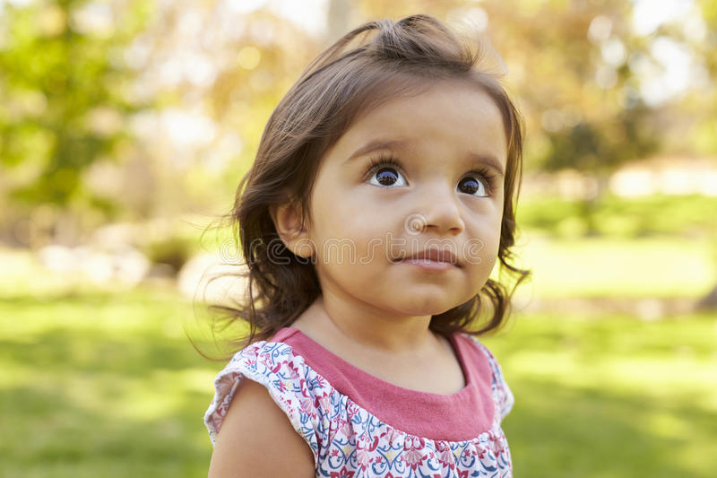 Mixed race Caucasian Asian toddler girl in a park, portrait royalty free stock photos