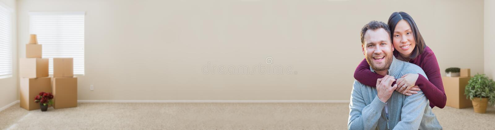 Mixed Race Caucasian and Chinese Couple Inside Empty Room with Boxes royalty free stock photo