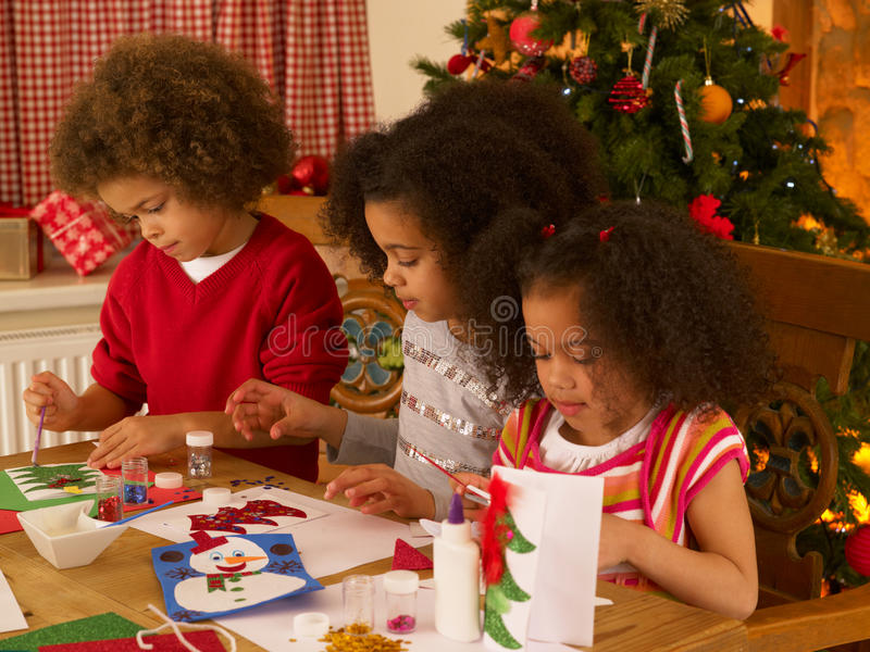 Mixed race children making Christmas cards stock photography
