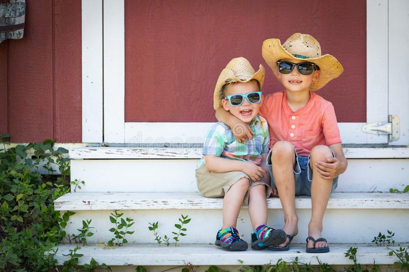 Mixed Race Chinese Caucasian Young Brothers Wearing Cowboy Hats stock photo