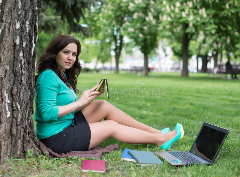 Mixed race college student lying down on the grass working royalty free stock images