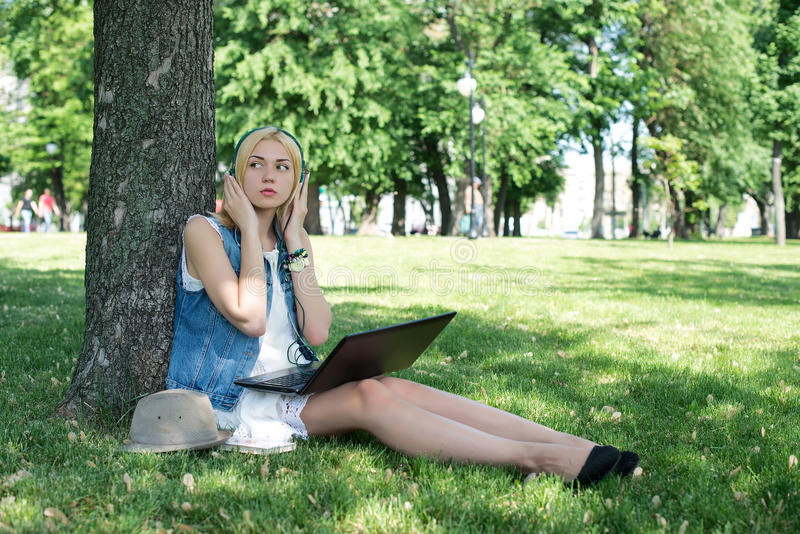 Mixed race college student sitting on the grass working. On laptop at campus royalty free stock image