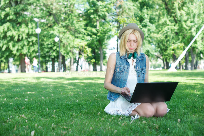 Mixed race college student sitting on the grass working. On laptop at campus stock photography