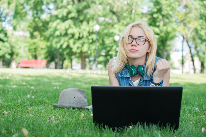 Mixed race college student sitting on the grass working. On laptop at campus royalty free stock photos