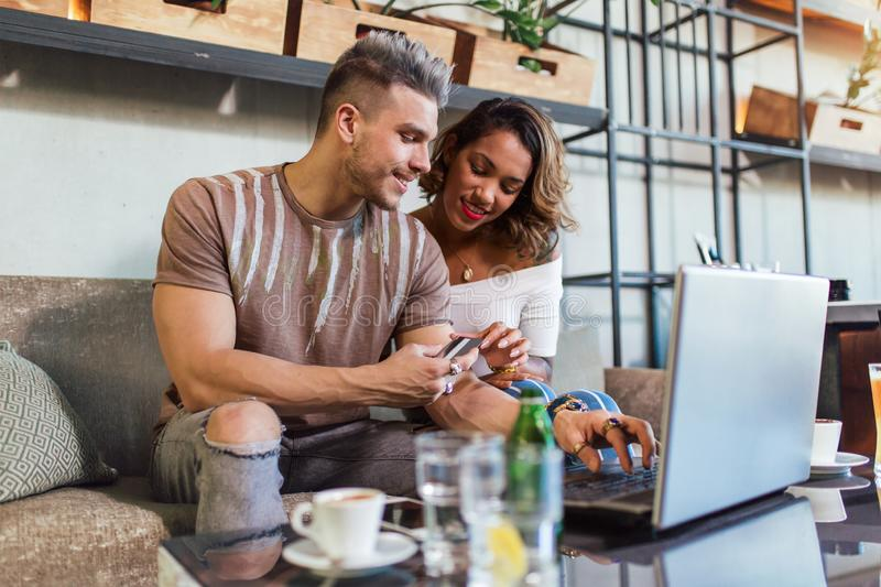 Mixed race couple buying online with credit card and laptop. In a coffee shop stock photography