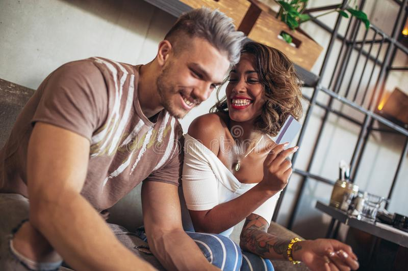 Mixed race couple buying online with credit card and laptop. In a coffee shop stock images