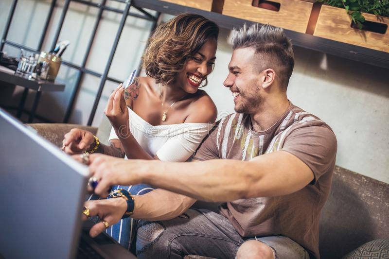 Mixed race couple buying online with credit card and laptop. In a coffee shop royalty free stock photos