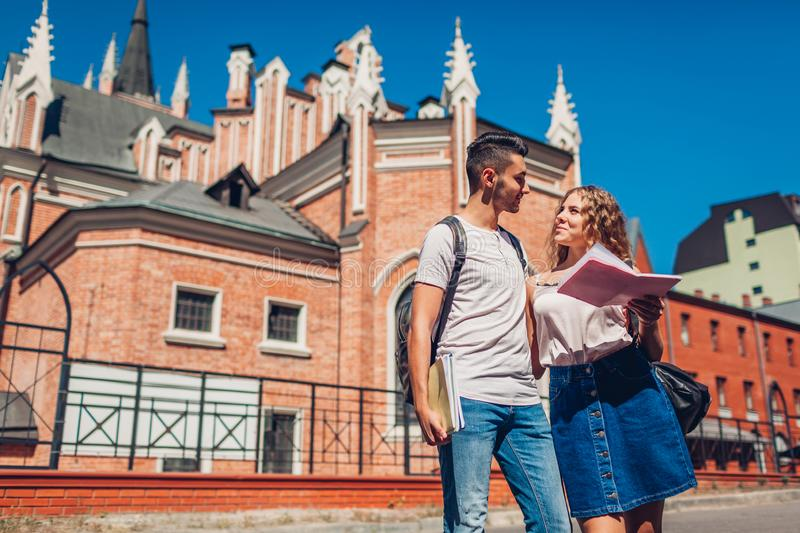 Mixed race couple of college students walking by university with copybooks. Young arab man and white woman studying royalty free stock photos