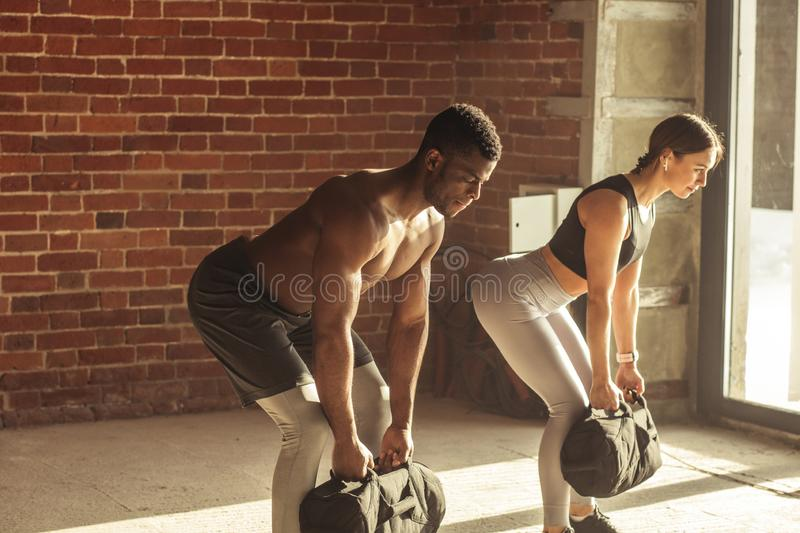 Mixed-race couple doing squats exercise, while holding in hands heavy sandbags. stock photography
