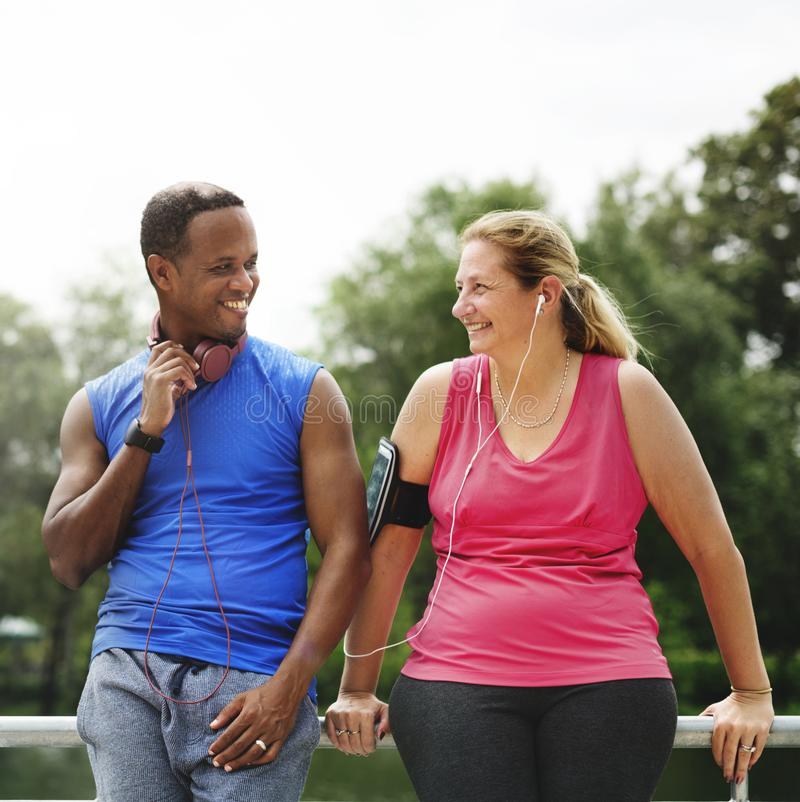 Mixed race couple exercising together in the park stock photography