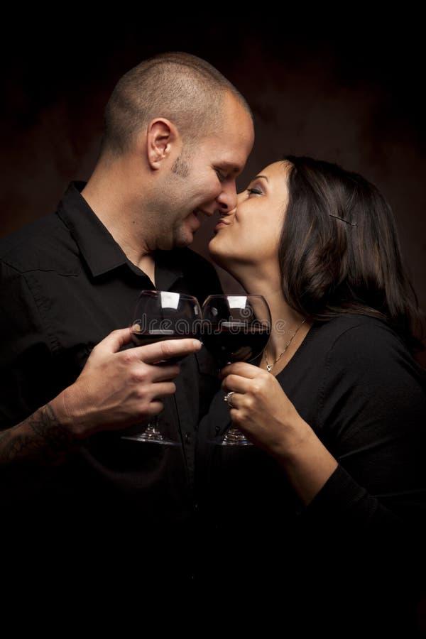 Mixed Race Couple Flirting Holding Wine Glasses stock photo