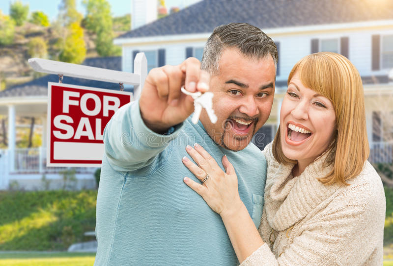 Mixed Race Couple With Keys in Front of Real Estate Sign and New. Happy Mixed Race Couple With Keys in Front of For Sale Real Estate Sign and New House royalty free stock images
