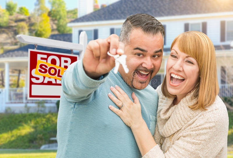 Mixed Race Couple With Keys in Front of Real Estate Sign and New. Happy Mixed Race Couple With Keys in Front of Sold For Sale Real Estate Sign and New House royalty free stock images