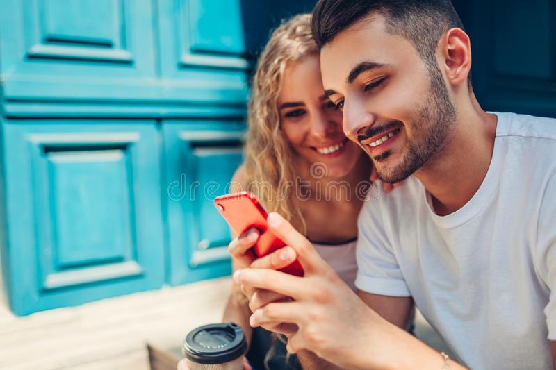 Mixed race couple in love walking in city. Arab man and white woman drinking coffee and using smartphone stock image