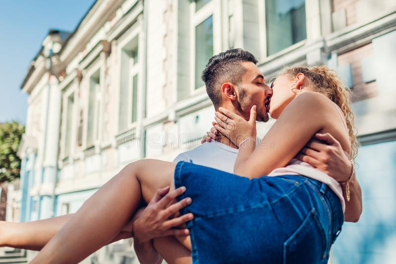 Mixed race couple in love walking in city. Arab man holding his girlfriend in hands. Young people hugging royalty free stock photography