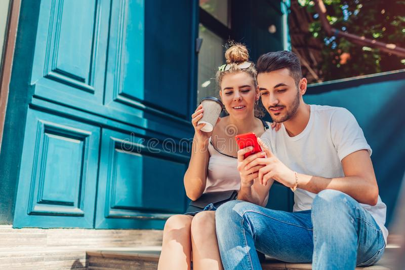 Mixed race couple in love walking in city. Arab man and white woman drinking coffee and using smartphone royalty free stock photo