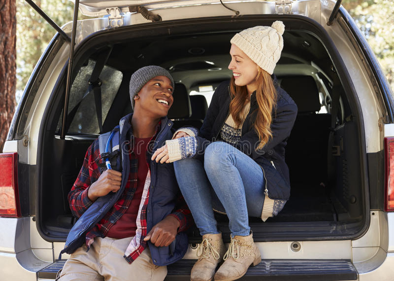 Mixed race couple in open back of car looking at each other stock image