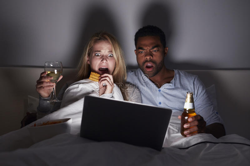 Mixed race couple watching scary film in bed on laptop stock images