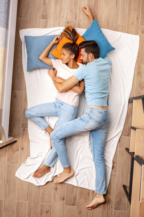 Mixed Race Couple. Young man and woman lying on bed top view hugging sleeping peaceful royalty free stock photos