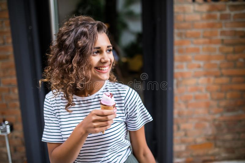 Mixed race curlu Woman eating Ice cream on vacation travel. Smiling girl having fun eating icecream outdoors during holidays . stock photos
