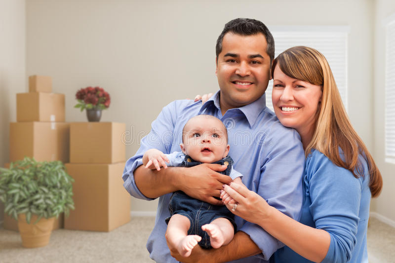 Mixed Race Family with Baby in Room with Packed Moving Boxes. Happy Mixed Race Family with Baby in Room with Packed Moving Boxes royalty free stock image