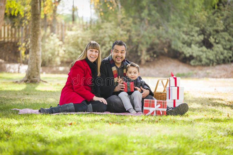 Mixed Race Family Enjoying Christmas Gifts in the Park Together stock photography