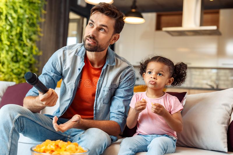 Mixed Race Family. Father and daughter sitting on sofa at home eating snacks holding mike ready for karaoke excited royalty free stock images