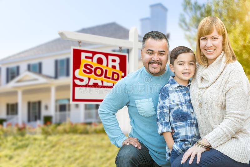 Mixed Race Family In Front of House and Sold For Sale Real Estate Sign. Happy Mixed Race Hispanic and Caucasian Family Portrait In Front of House and Sold For royalty free stock image