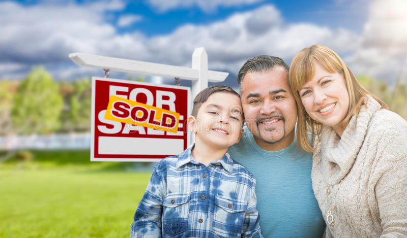 Mixed Race Family In Front of House and Sold For Sale Real Estate Sign. Mixed Race Family In Front of House and a Sold For Sale Real Estate Sign royalty free stock photos
