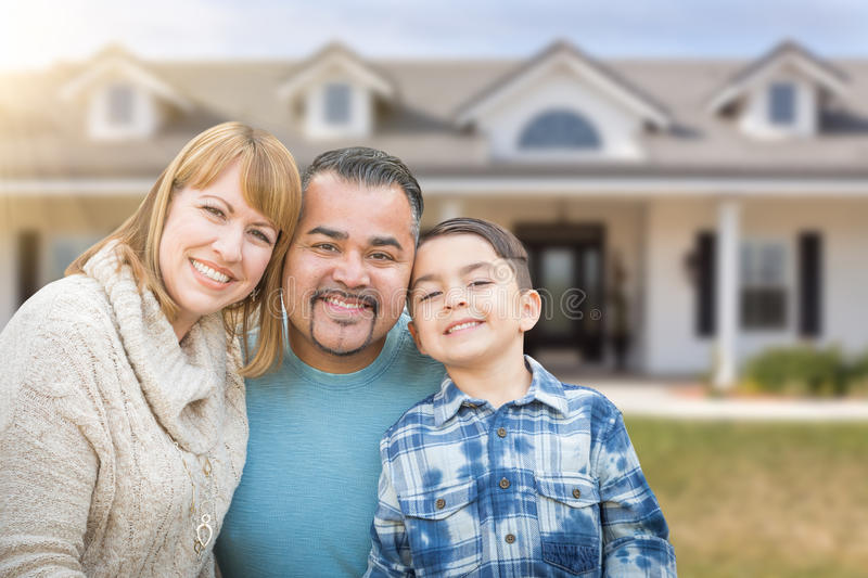 Mixed Race Family In Front Yard of Beautiful House and Property. Mixed Race Family In Front Yard of a Beautiful House and Property stock image