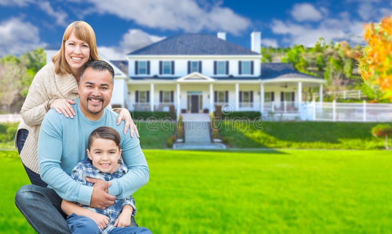 Mixed Race Family In Front Yard of Beautiful House and Property. Mixed Race Family In Front Yard of a Beautiful Stately House and Property stock image