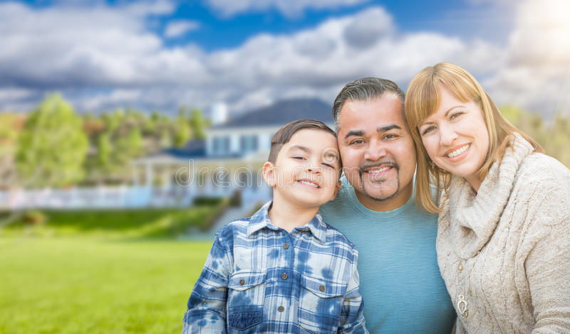Mixed Race Family In Front Yard of Beautiful House and Property. Mixed Race Family In Front Yard of a Beautiful Stately House and Property royalty free stock images