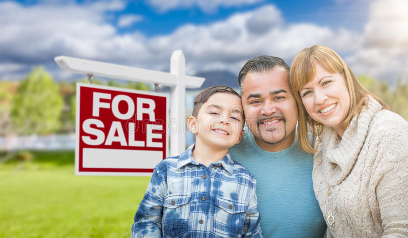 Mixed Race Family Portrait In Front of House and For Sale Real E. Mixed Race Family Portrait In Front of a House and For Sale Real Estate Sign royalty free stock photos