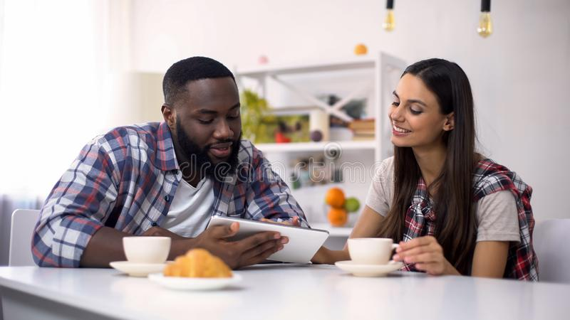 Mixed-race family scrolling on tablet pc during breakfast, shopping online stock photo