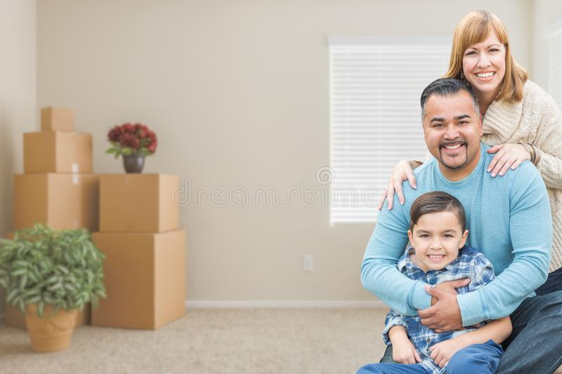 Mixed Race Family with Son in Room with Packed Moving Boxes. Happy Mixed Race Family with Son in Room with Packed Moving Boxes stock photo