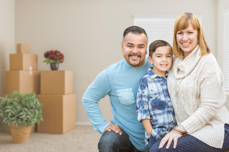 Mixed Race Family with Son in Room with Packed Moving Boxes. Happy Mixed Race Family with Son in Room with Packed Moving Boxes royalty free stock photo