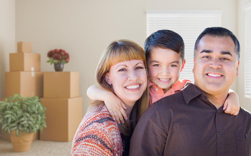 Mixed Race Family with Toddler in Room with Packed Moving Boxes. Happy Mixed Race Family with Baby in Room with Packed Moving Boxes royalty free stock photos