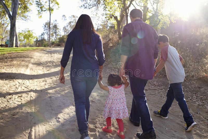 Mixed race family walking on rural path, backlit back view royalty free stock images
