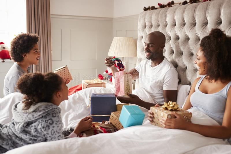 Mixed race family watching dad opening a gift in bed on Christmas morning, close up royalty free stock photography