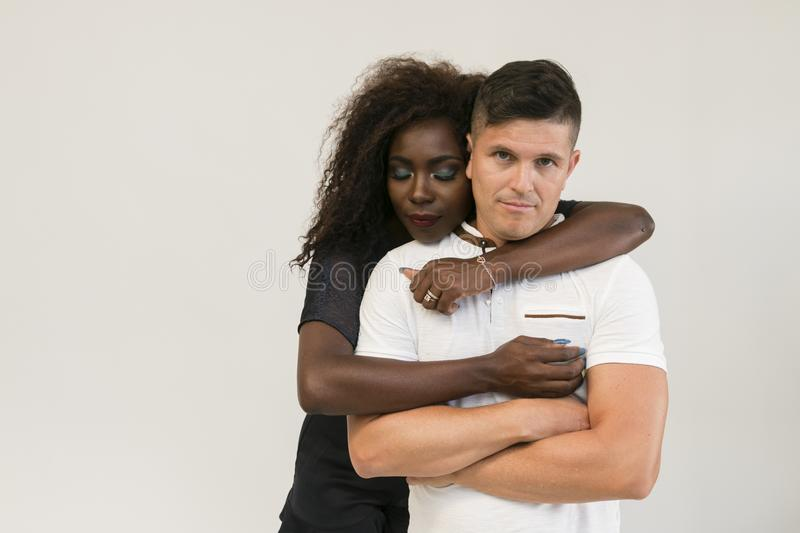 Mixed race family. Young tender wife hugging his husband. Loving royalty free stock photo