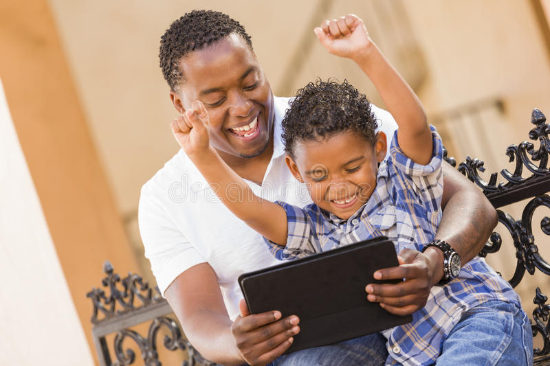 Download Mixed Race Father And Son Using Touch Pad Tablet Stock Image - Image: 25651359