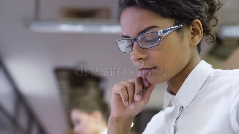 Mixed race female in eyeglasses thinking about project at office, new ideas royalty free stock photos