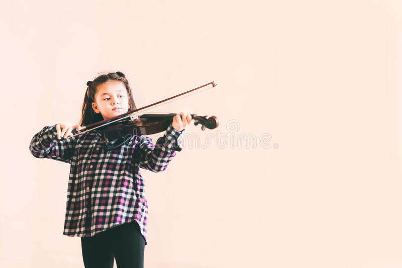 Mixed race female kid playing violin, child education or music concept, with copy space stock images