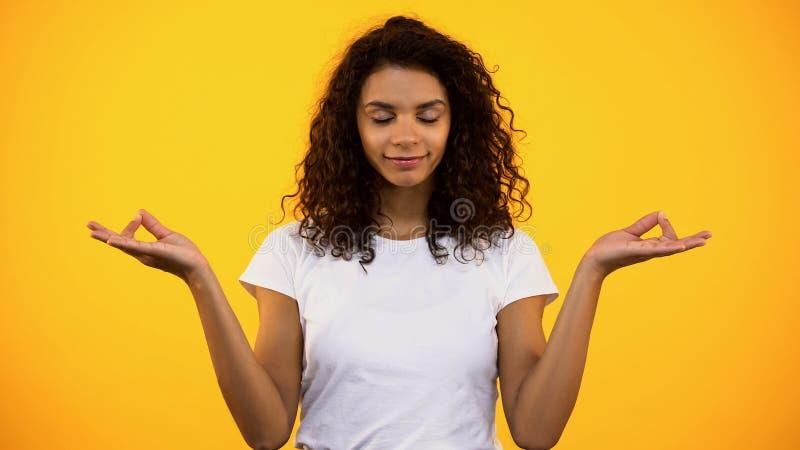 Mixed-race female meditating on bright background, practicing yoga, health care royalty free stock image